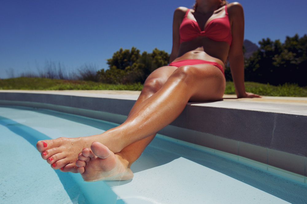 Low angle view of female model relaxing by the pool with her legs in water. Young woman in bikini sunbathing by swimming pool.