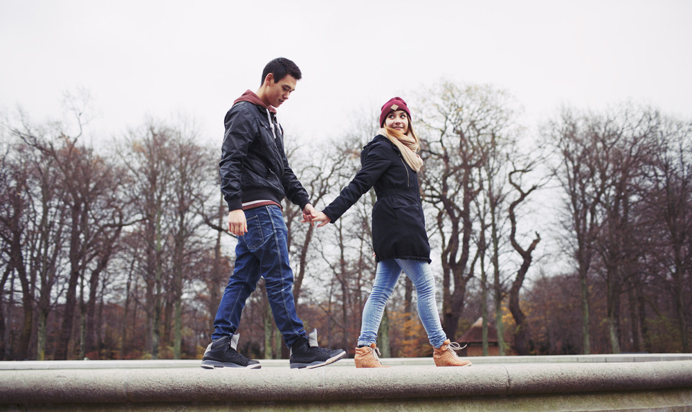 Low angle view of handsome young man with his girlfriend walking together holding hands in park. Mixed race teenage couple in love.