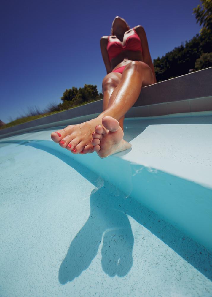 Low angle view of young woman wearing bikini enjoying the sun by the pool. Female model sunbathing by swimming pool.
