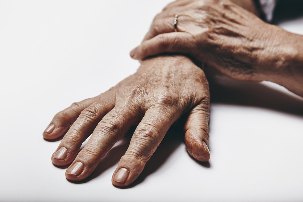 Macro of old woman hands on a grey surface. Focus on fingers of senior female.