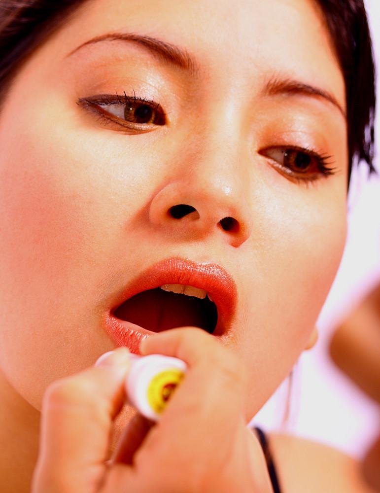 Making Herself More Beautiful By Applying Lipstick