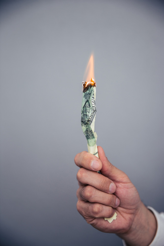 Male hand holding a burning US dollar bill