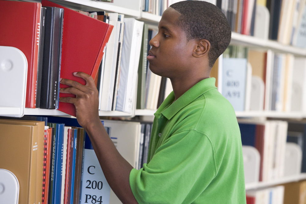 Male student selecting book from library shelf