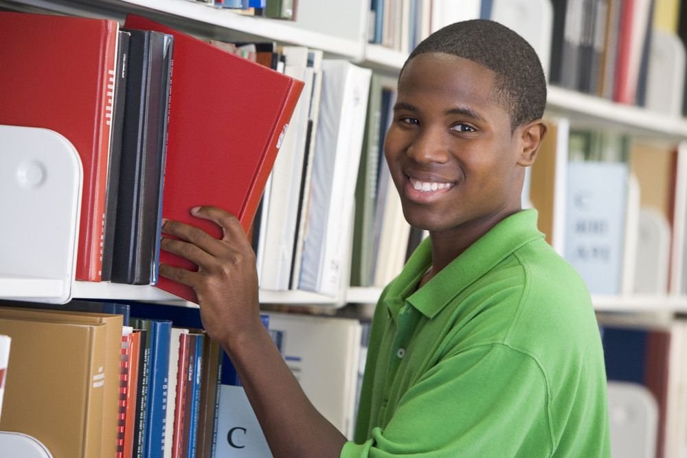 Male student selecting book in library