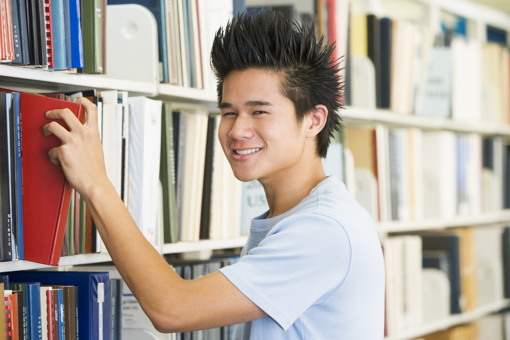 Male university selecting book from library shelf