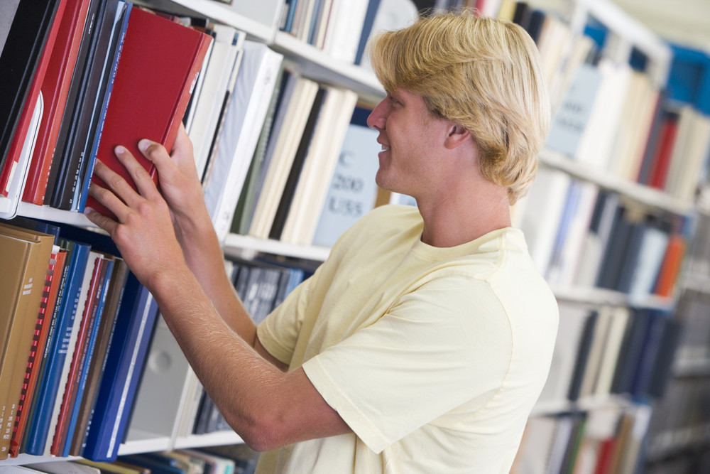 Male university student selecting book from library shelf