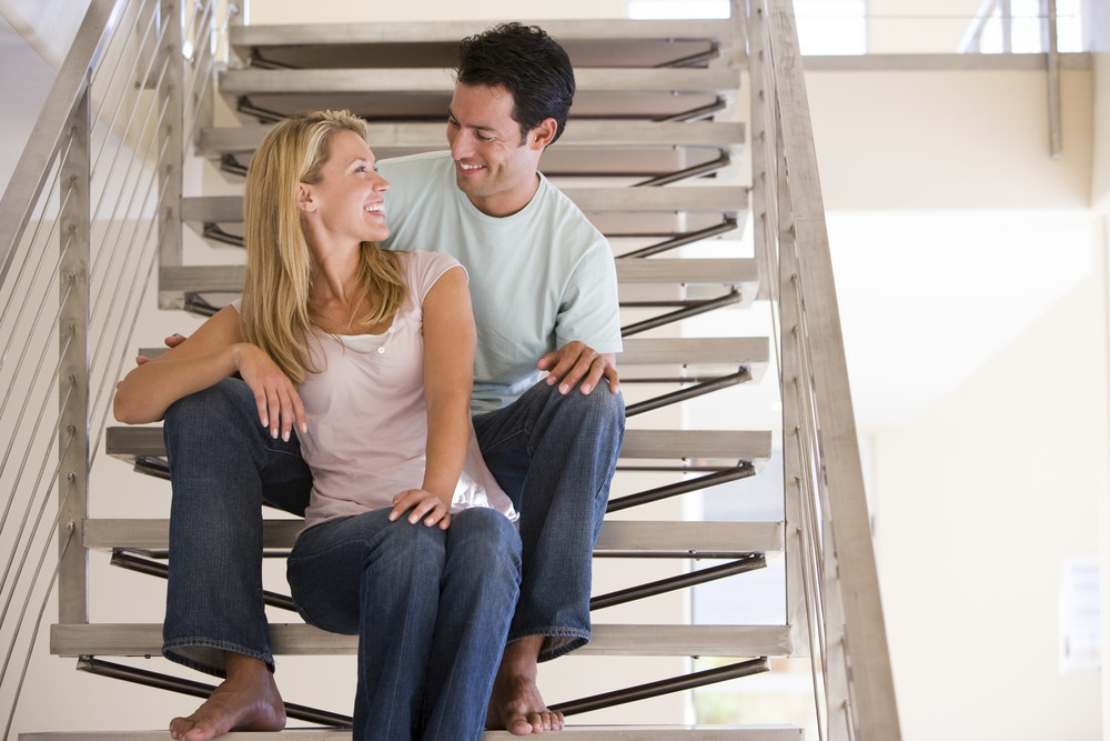 man and women sat on stairs indoors