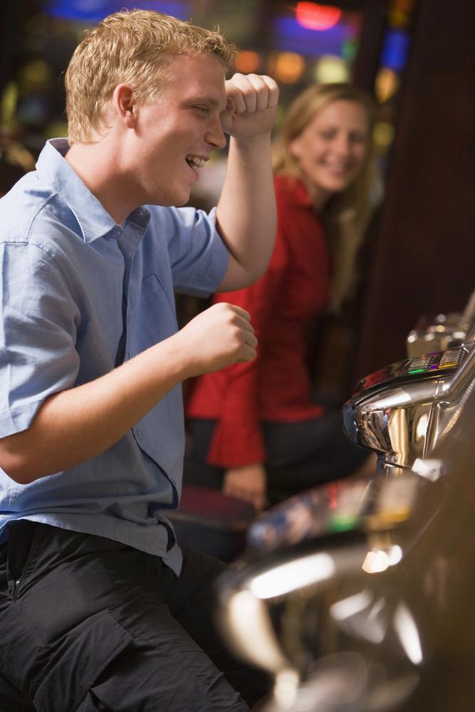 Man celebrating win at slot machine in casino