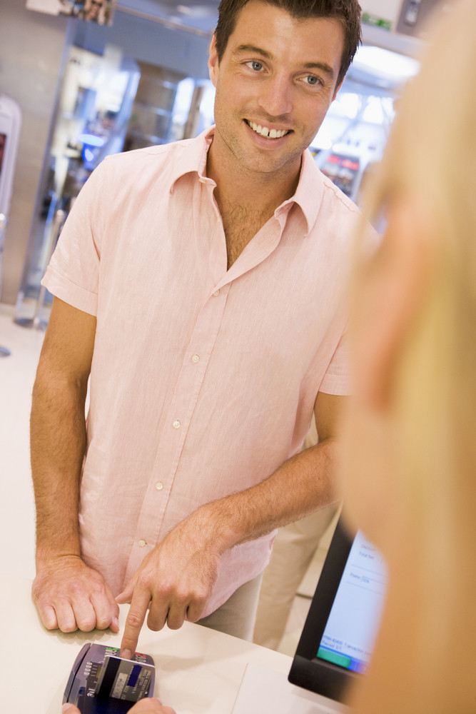 Man entering security details for credit card transaction in store