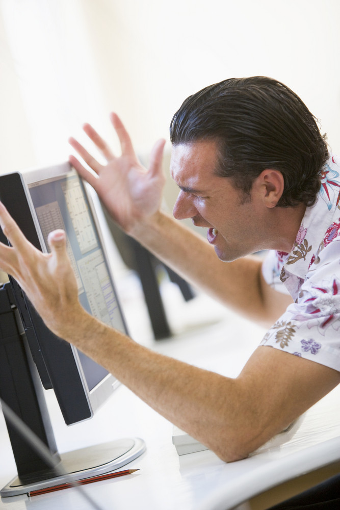 Man in computer room frustrated at monitor