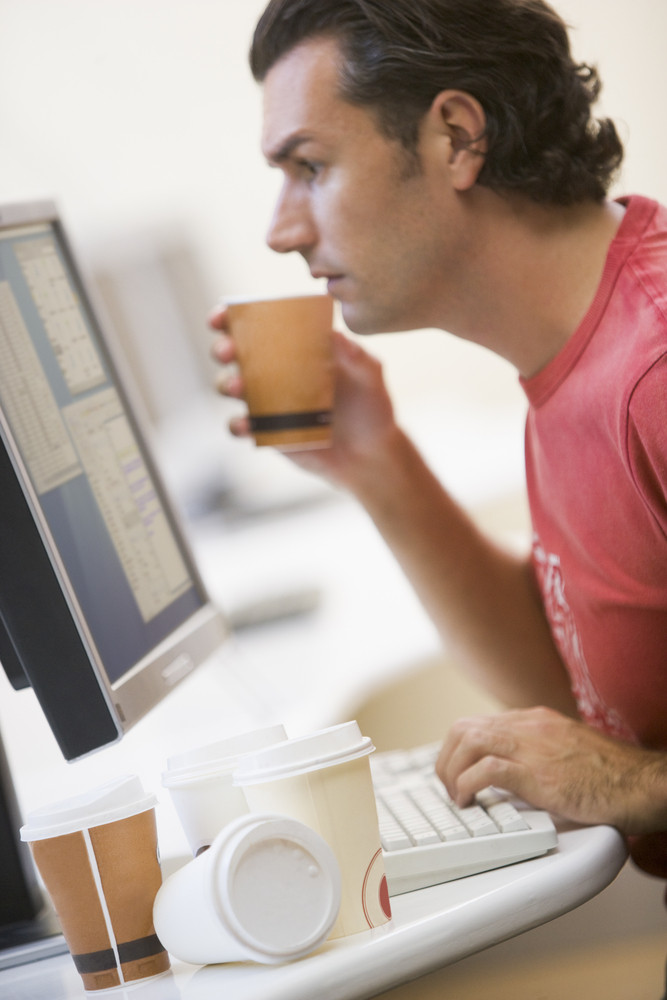 Man in computer room with many empty cups of coffee