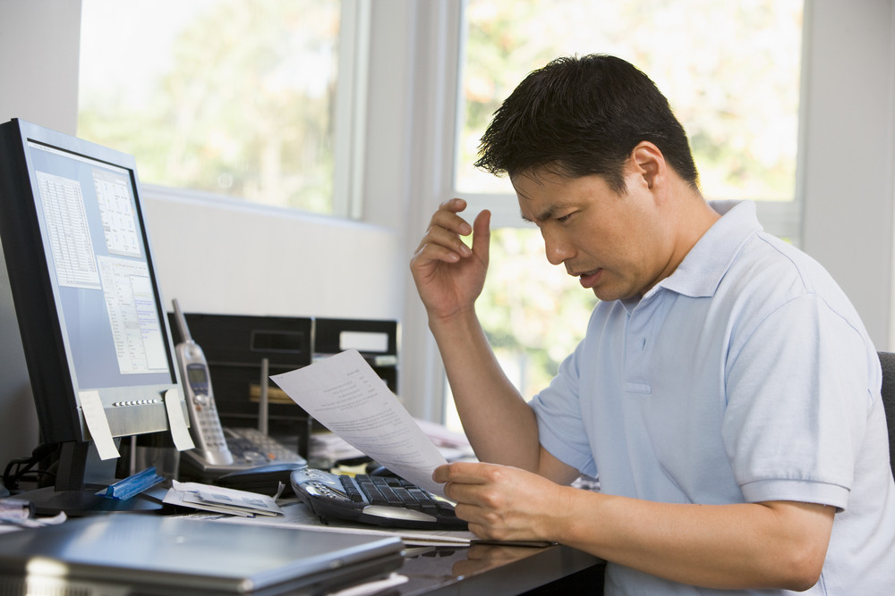 Man in home office with computer and paperwork frustrated