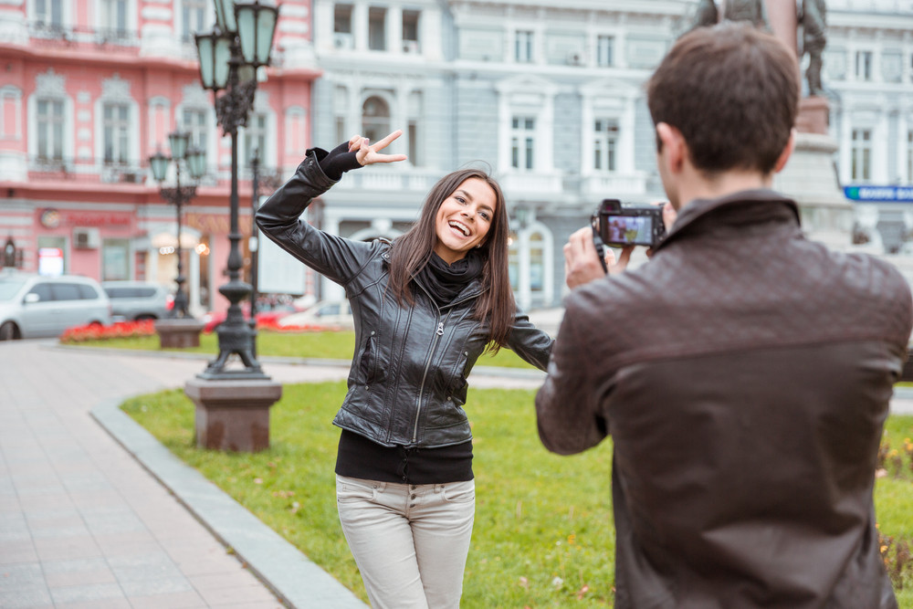 Man making photo of laughing woman outdoors