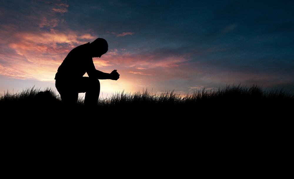 Man praying in the grassy field