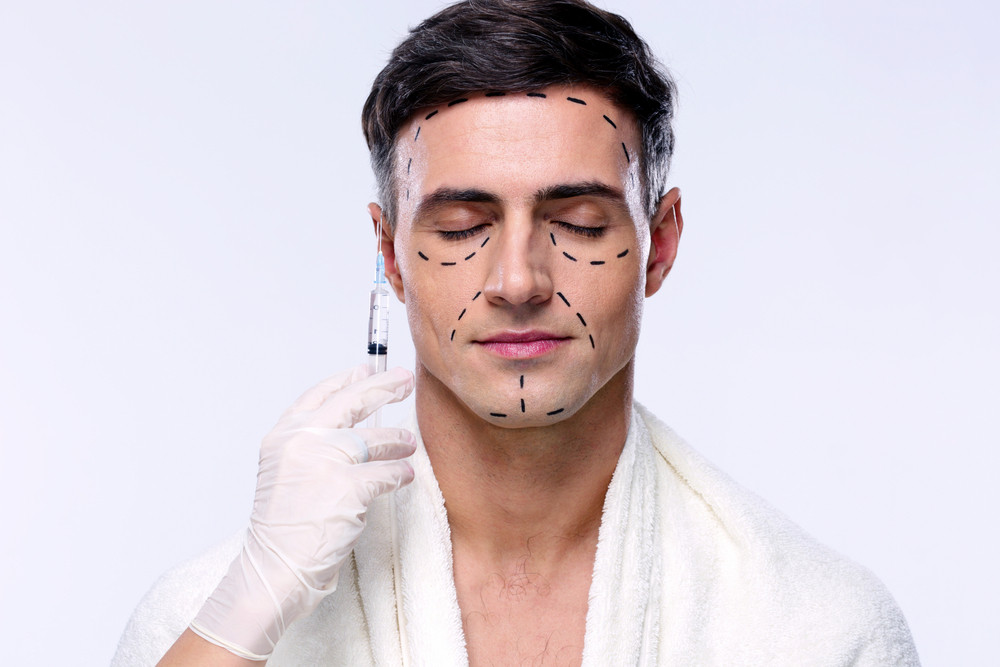Man preparing for plastic surgery over gray background