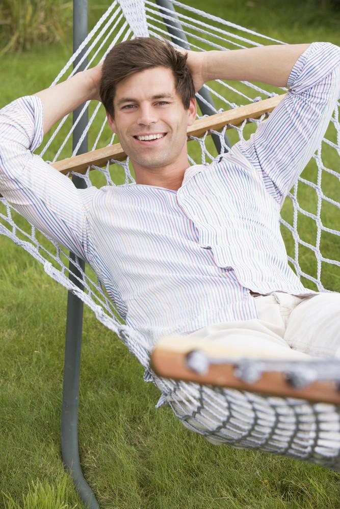 Man relaxing in hammock smiling