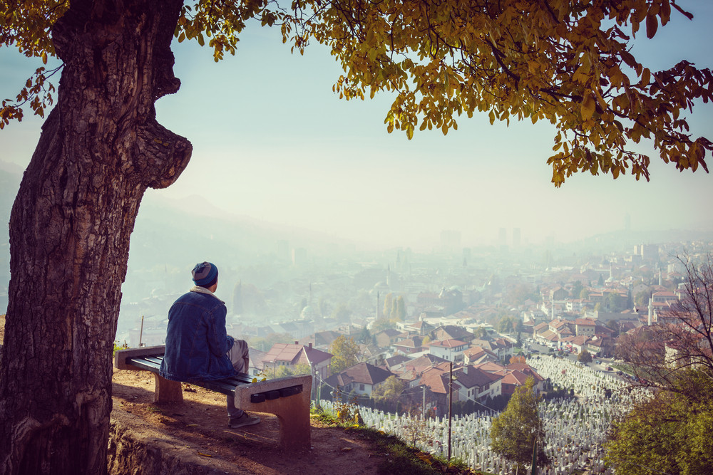 man sitting alone on bench and watching the city royalty free stock
