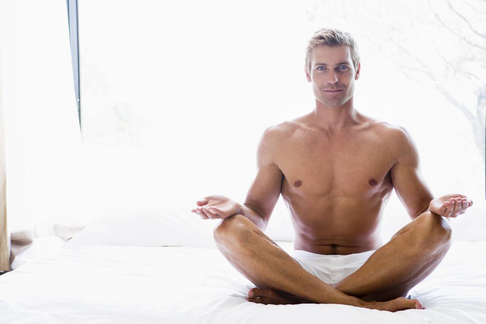 Man sitting on bed doing yoga