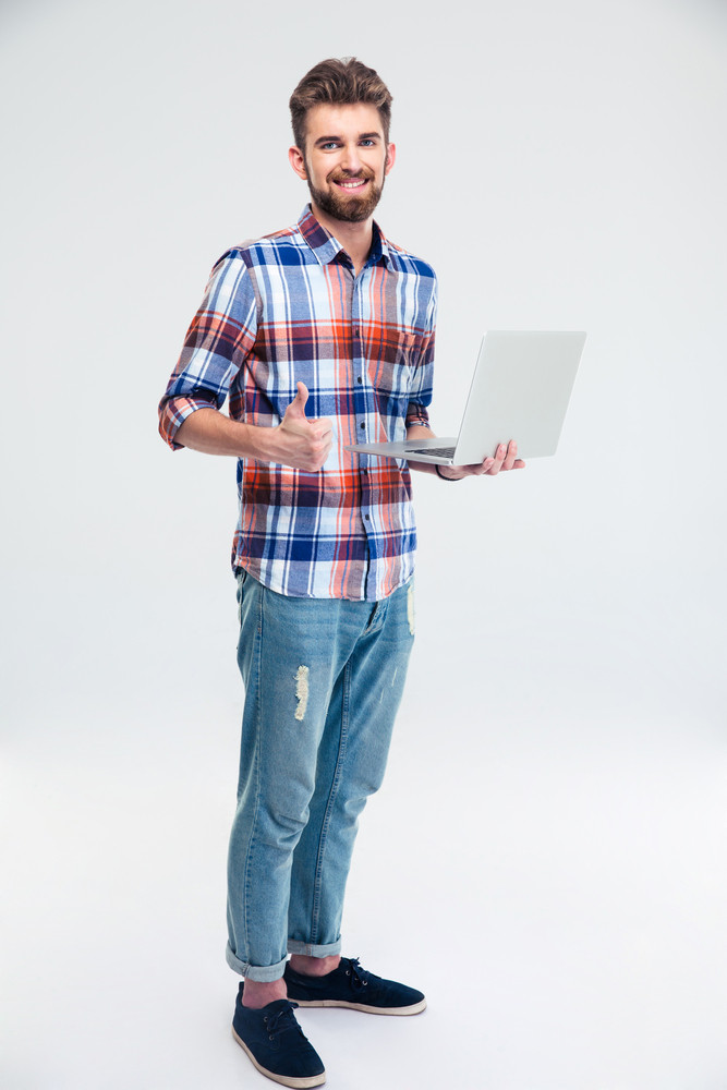 Man standing with laptop and showing thumb up sign