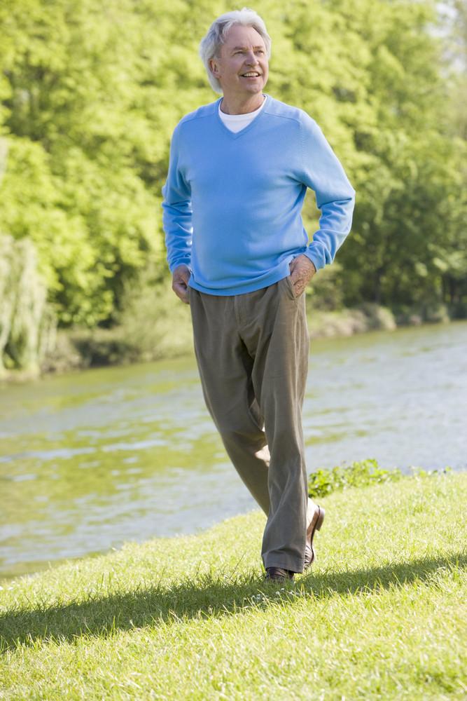 Man walking outdoors at park by lake smiling
