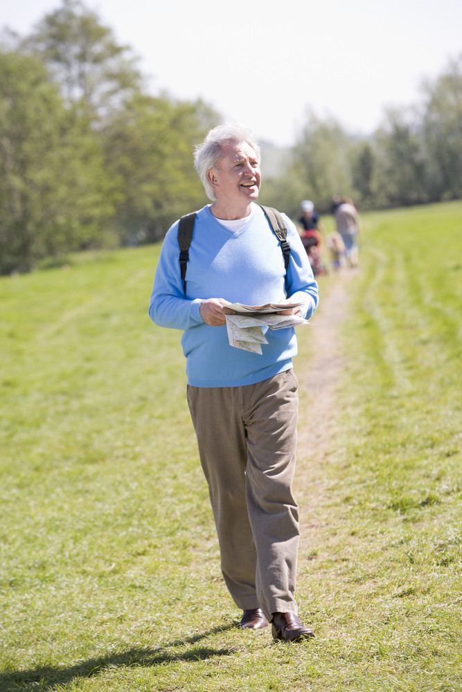 Man walking outdoors holding map smiling with people in background