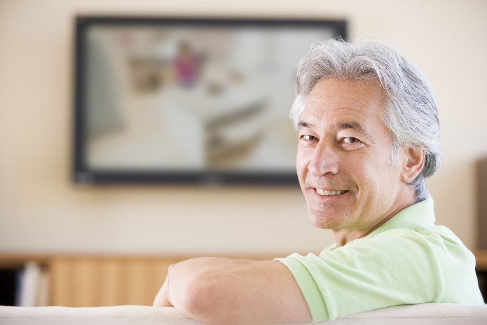 Man watching television smiling