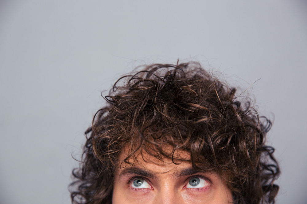 Man with curly hair looking up at copyspace