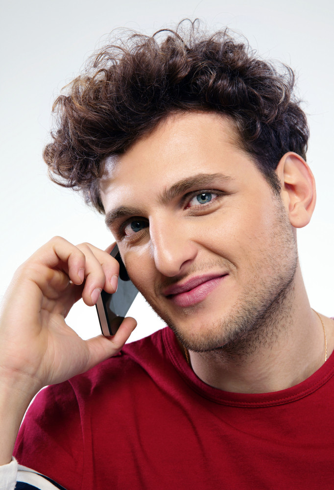 Man with curly hair talking on the phone