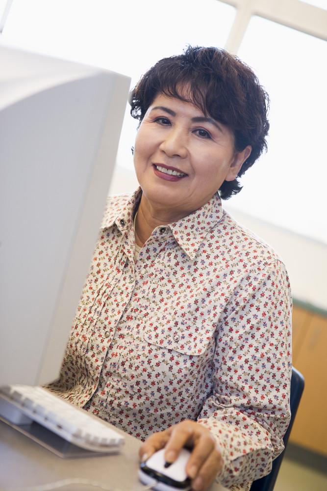 Mature female student learning computer skills