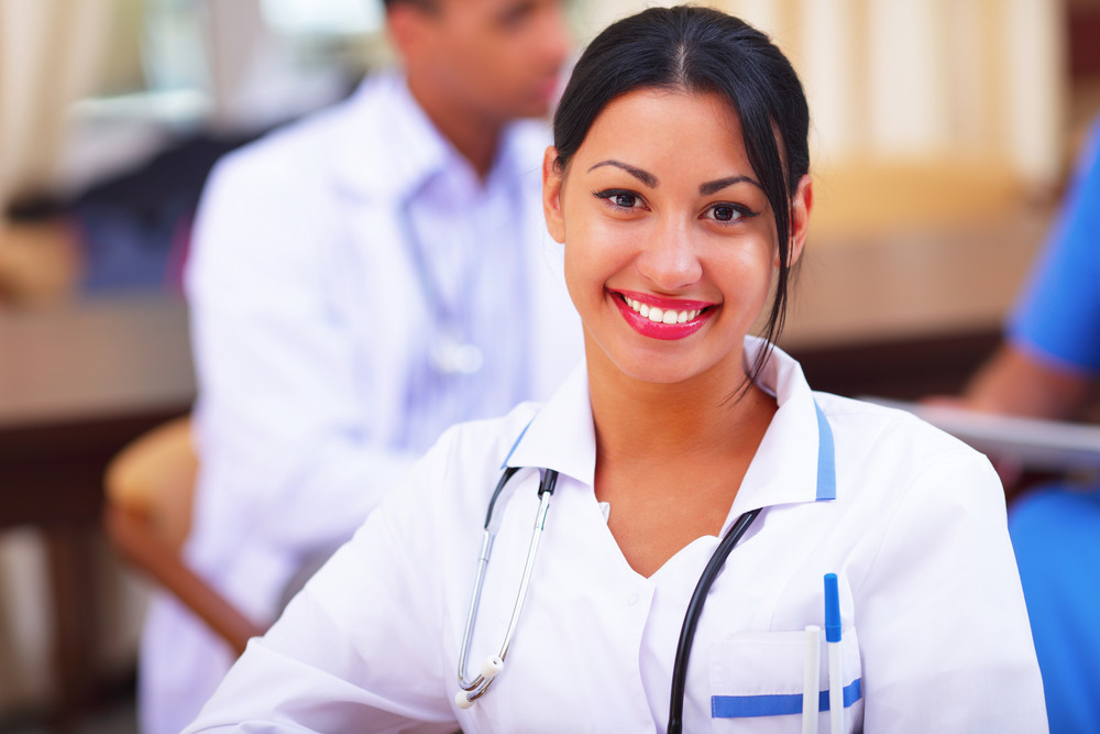 Medical doctor woman smiling indoors with her collegues working behind