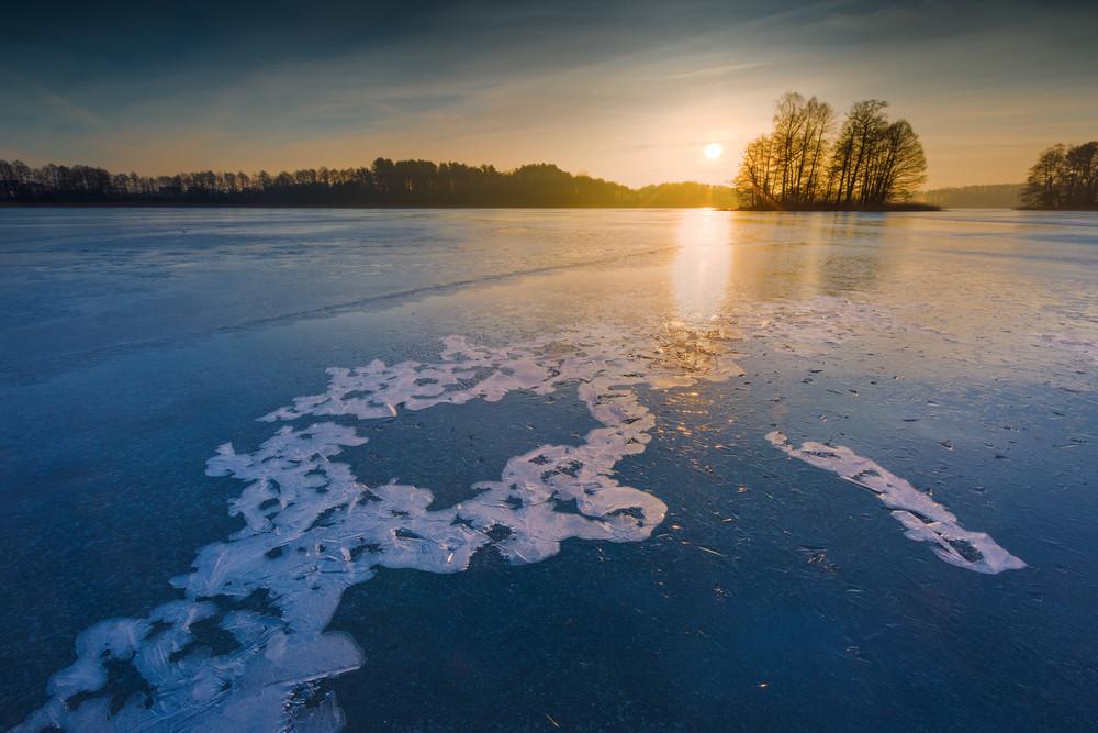 Frozen lake at sunrise landscape. Beautiful landscape of winter lake in Mazury lake district.
