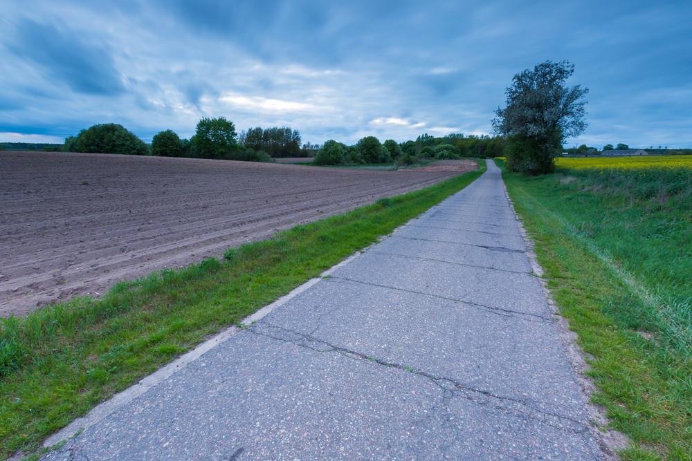 rural destroyed asphalt road in calm countryside springtime