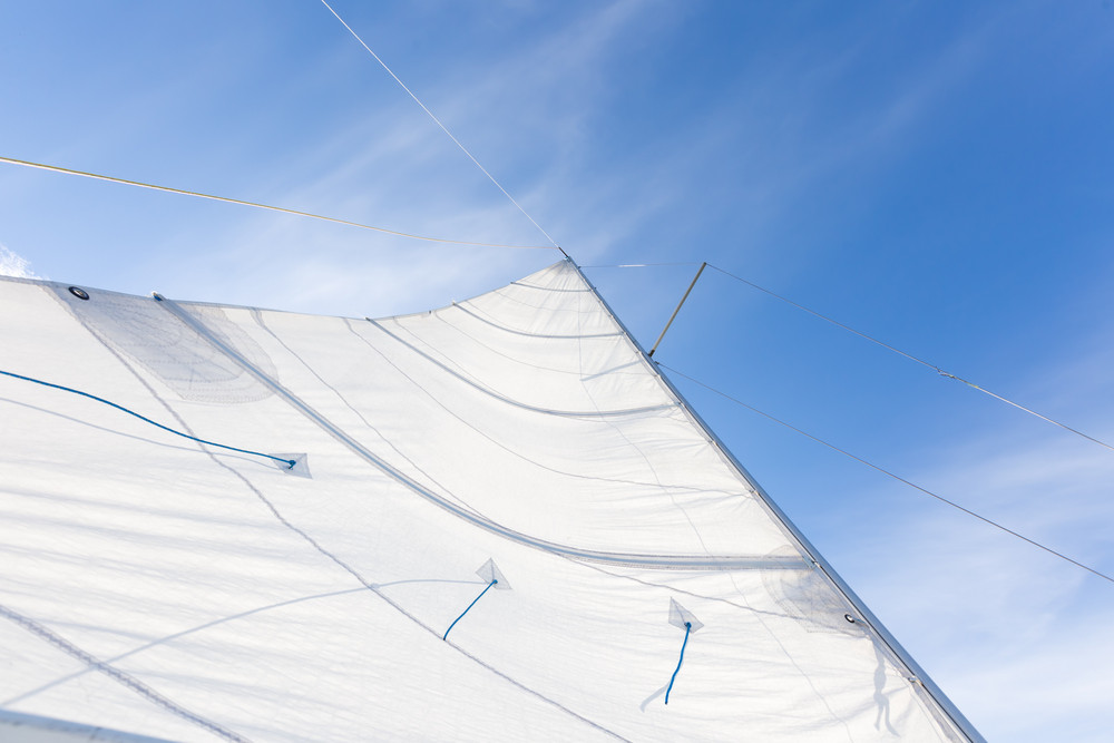 Close up of yacht mast and sail on sky background. Sailing boat part.