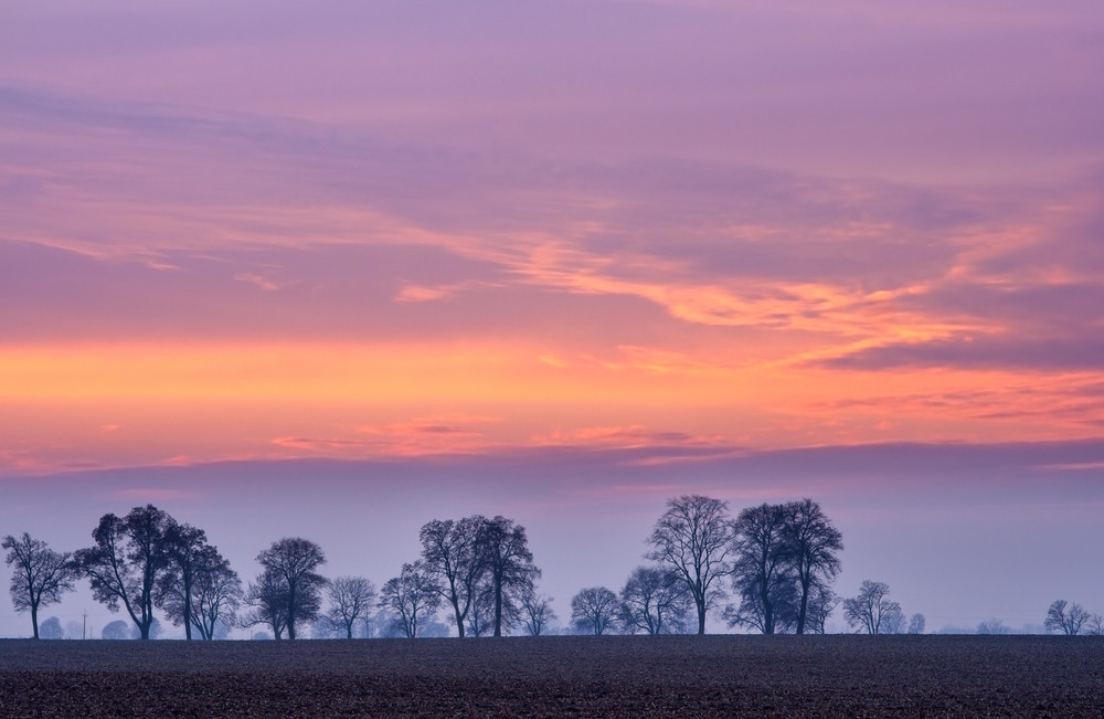 Beautiful magical after sunset colorful sky over fields
