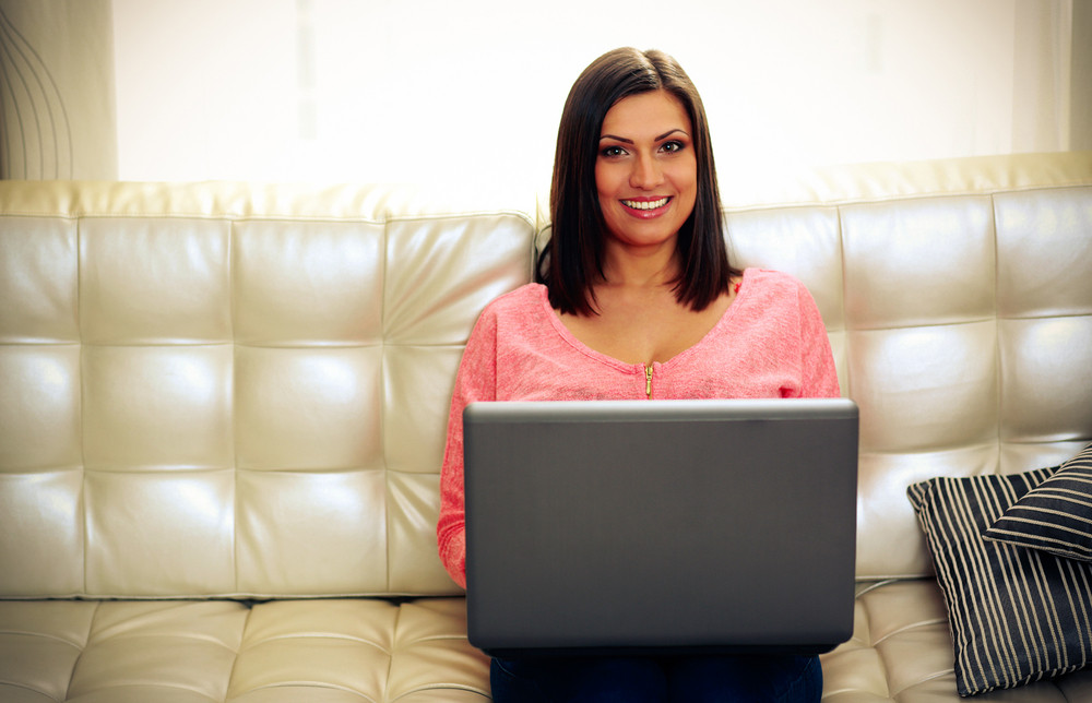 Middle-aged smiling woman sitting on the sofa with laptop at home