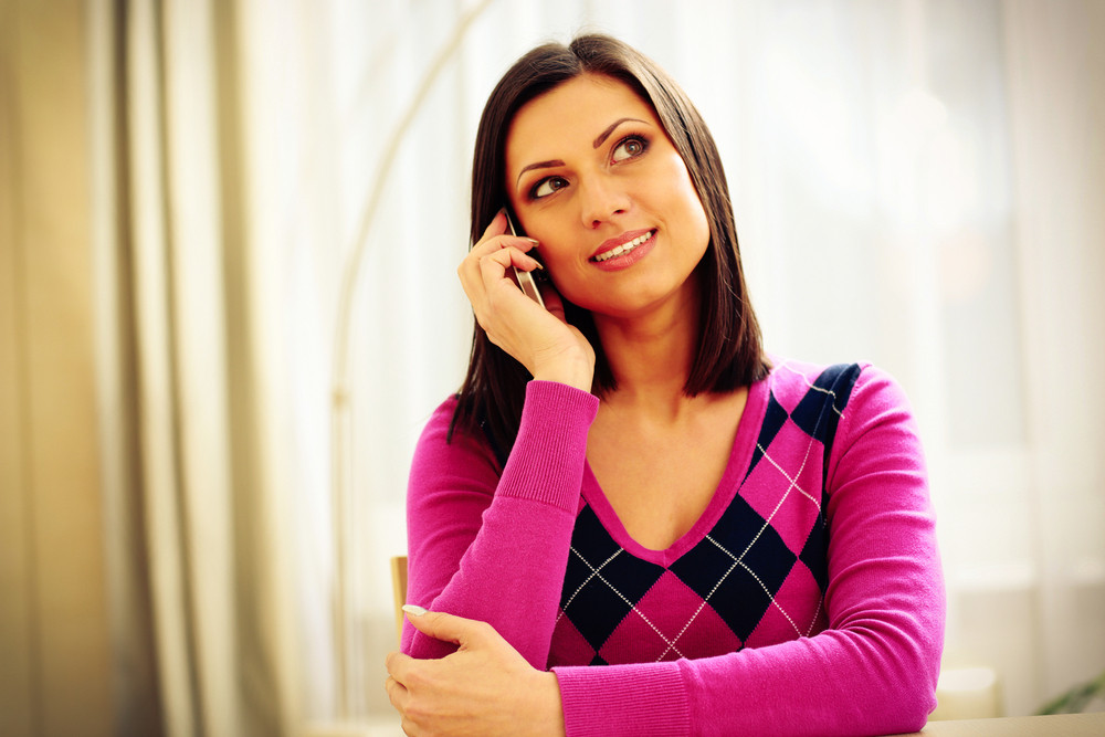 Middle-aged thoughtful woman talking on the phone and looking away
