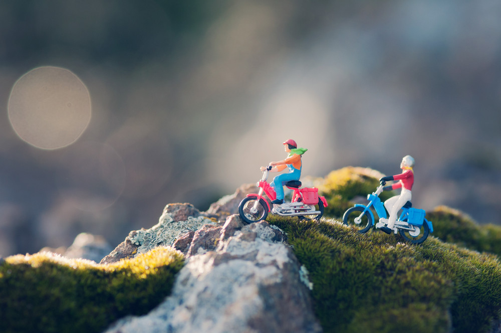 Miniature Couple Traveling Through The Countryside On Vintage Motorcycles At Dawn