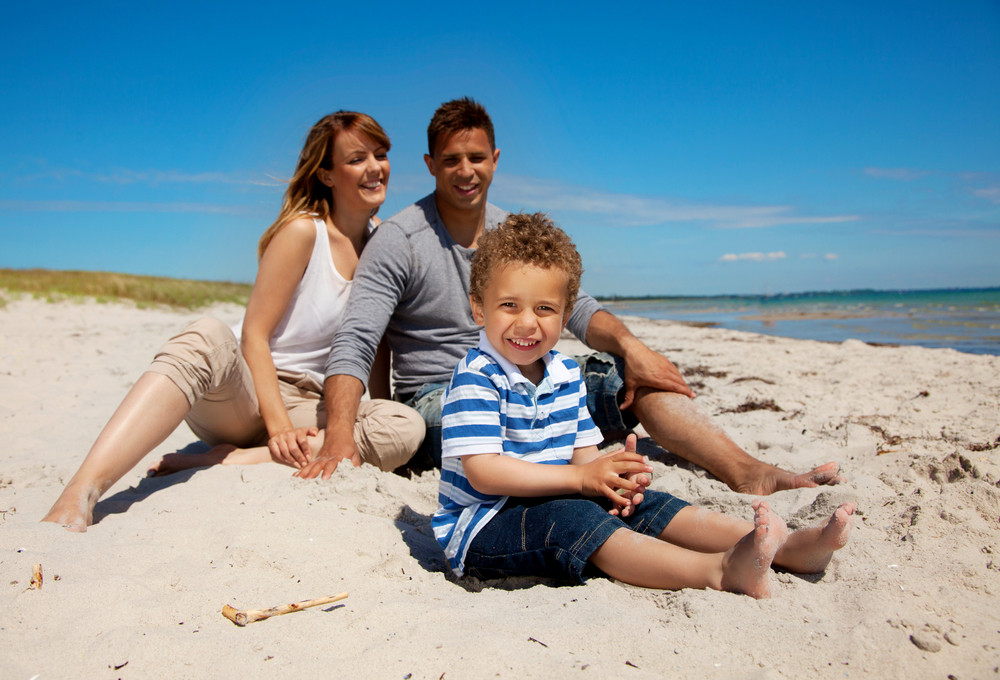 Mixed race family enjoys the weekend on a beach