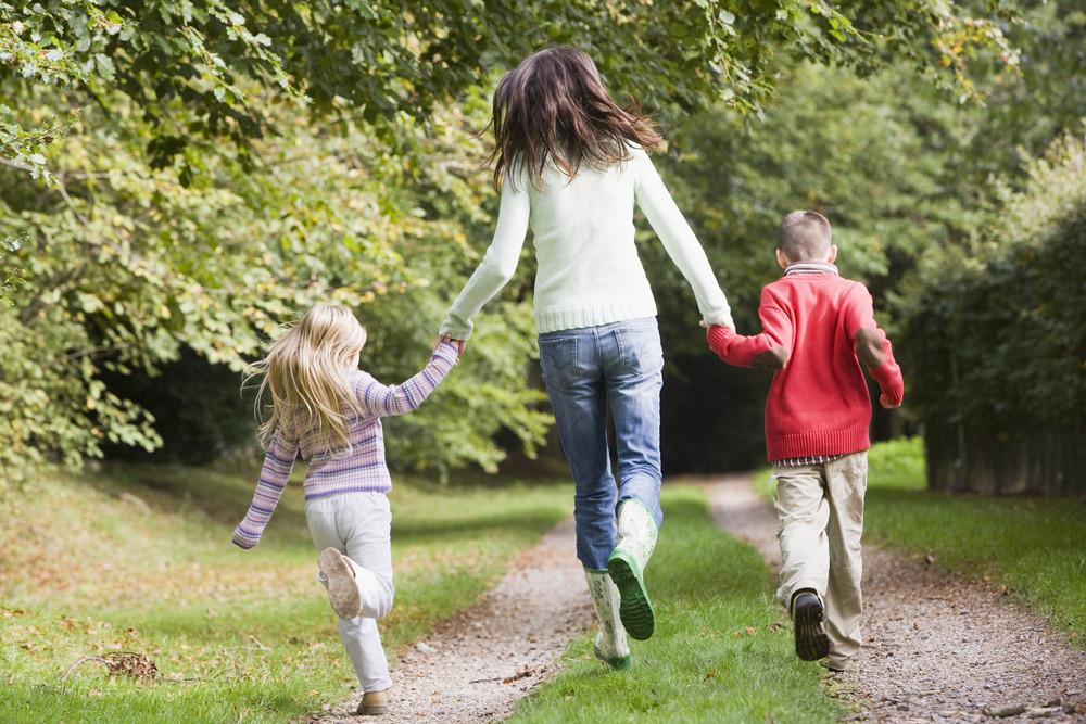 母親和孩子們在林地沿秋路徑運行