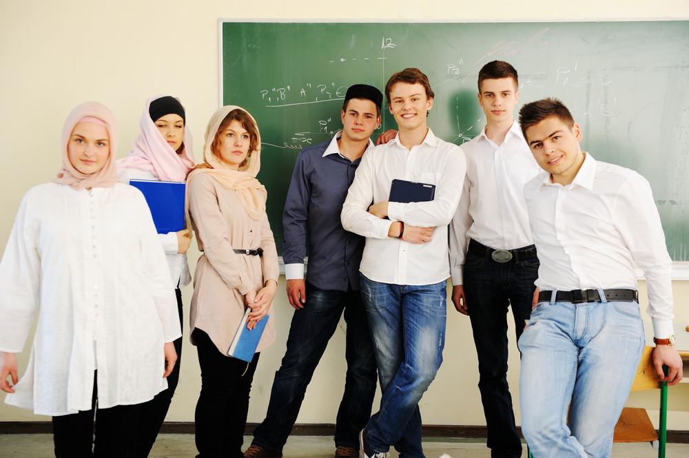Multi ethnic group of teenage students inside the high school classroom posing on board