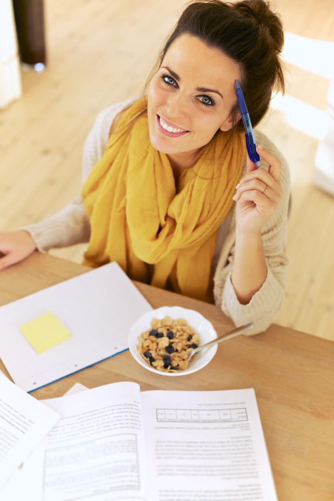 Multitasking student having her breakfast while studying