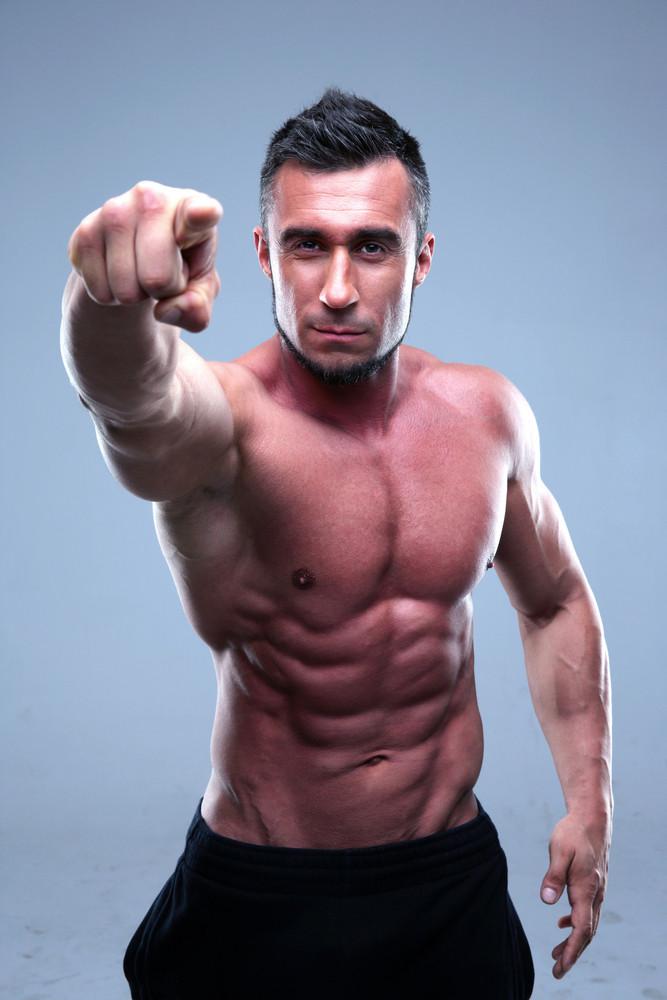 Muscular man pointing at the camera