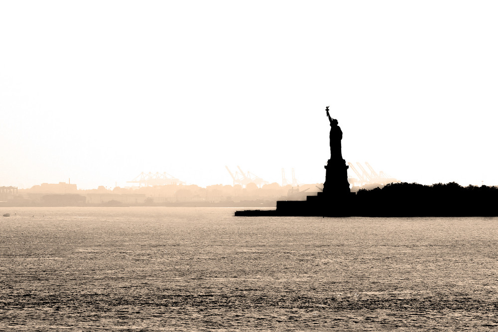New York harbor on a hazy day with a silhouette of the statue of liberty in the background.