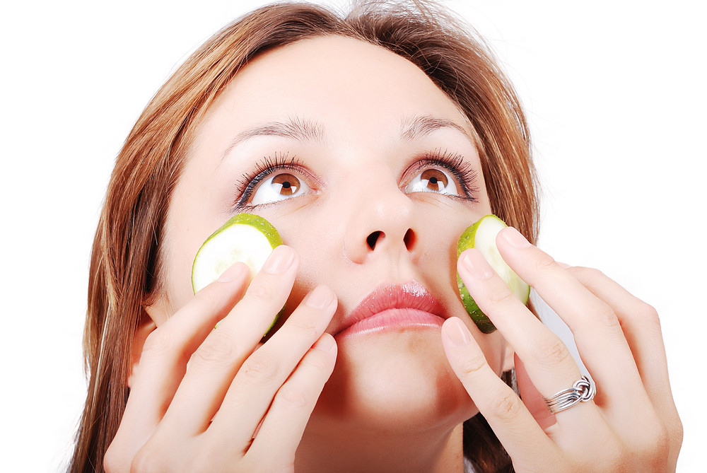 Nice female model with cucumber on face