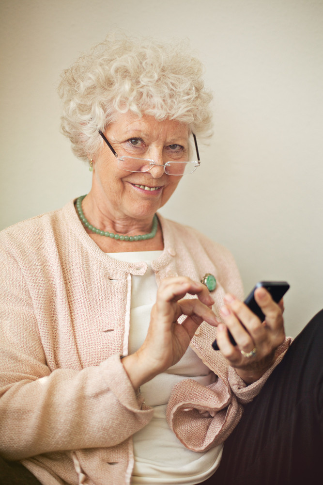 Old lady texting someone using her cell phone
