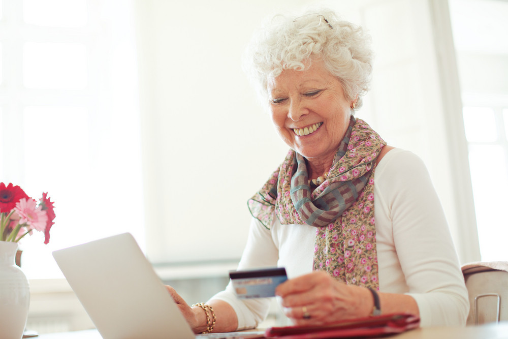 Old woman happy doing her shopping online using a credit card