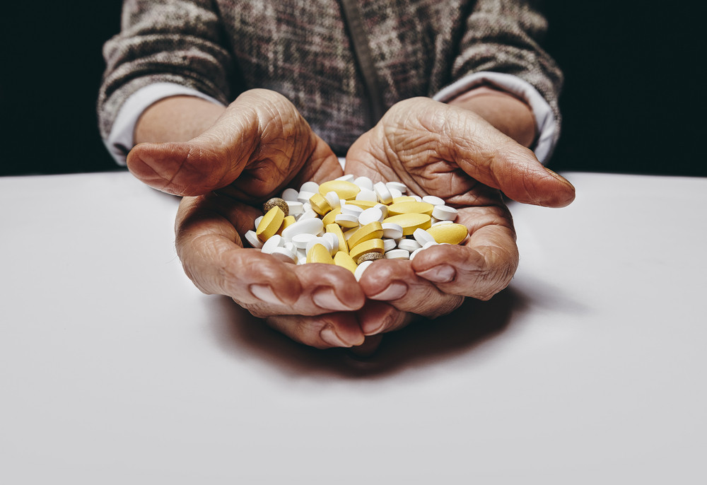 Old woman holding pills and medicine while sitting at a table. Focus on hands and pills. Close-up shot of senior female hands holding pills.