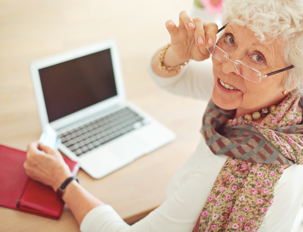 Old woman with credit card in front of her laptop looking at you