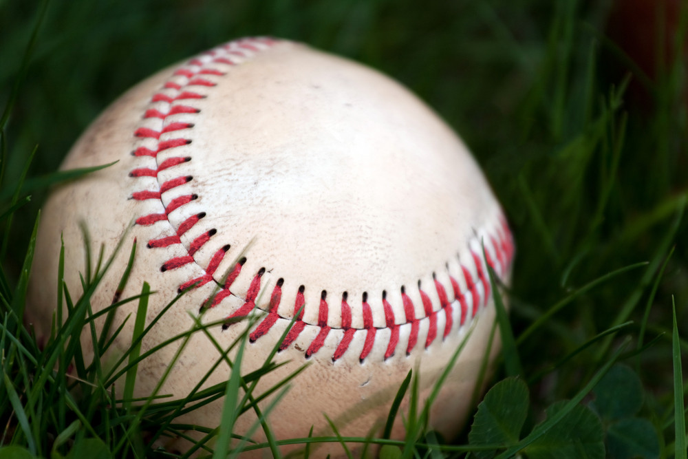 One aged and worn baseball sitting in the green grass.