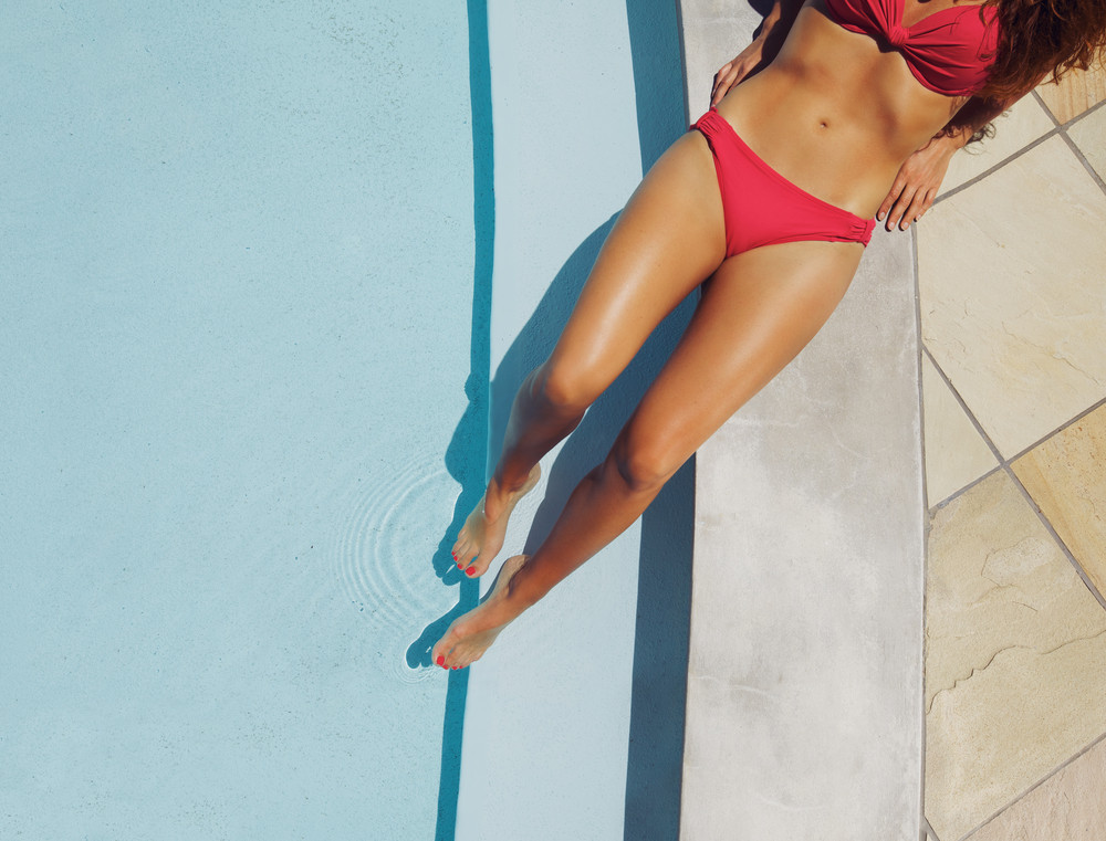 Overhead view of a beautiful female fashion model wearing red bikini resting on the edge of a pool at a luxury resort. Young caucasian lady sunbathing.